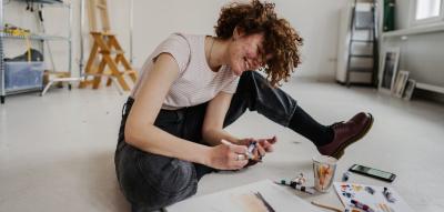 Frau sitzt auf dem Boden ihres Ateliers und malt