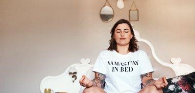 Eine junge Frau meditiert zuhause.