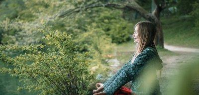 Achtsamkeit im Alltag: Frau meditiert im Wald