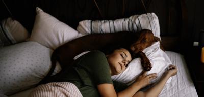 Frau schläft auf der Seite mit Hund im Bett