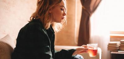 Frau sitzt auf dem Sofa mit Tee