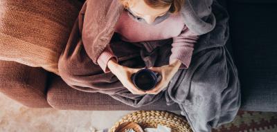 Frau auf dem Sofa in eine Wolldecke gehüllt