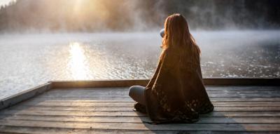 Frau sitzt zum Sonnenaufgang am See