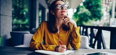 Perfektionismus überwinden: Frau sitzt am Schreibtisch