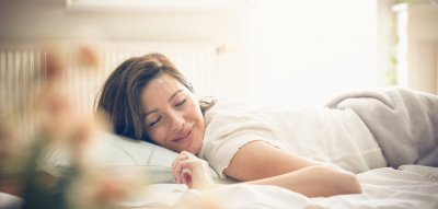 Frau liegt glücklich im Bett – Selbstliebe