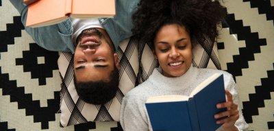 Paar auf dem Boden, liest ein Buch