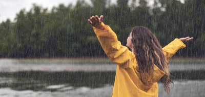 Frau steht mit gelber Regenjacke und erhobenen Armen im Regen