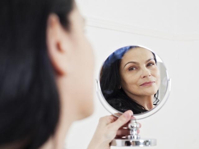 Reife Frau betrachtet sich zufrieden im Spiegel