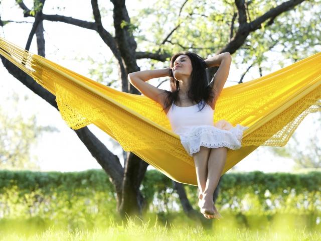 Frau entspannt im Sommer in der Hängematte