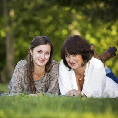 Mutter und Tochter liegen auf dem Bauch im Gras