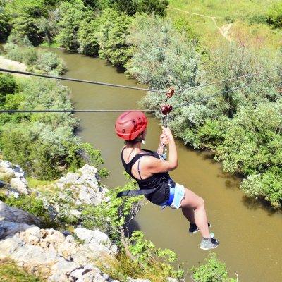 Frau von hinten beim Ziplining über Fluss
