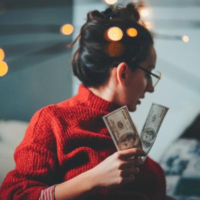 Frau hat zwei Geldscheine in der Hand
