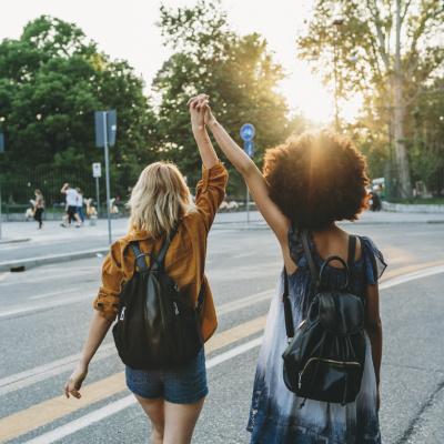 Zwei junge Frauen laufen mit erhobenen Händen durch die Straße