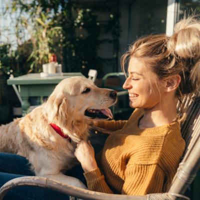 Frau sitzt auf ihrem Balkon mit Hund