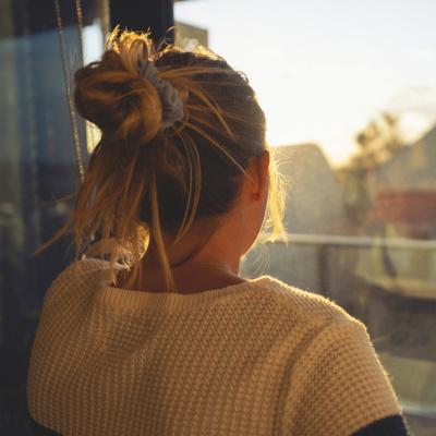 Frau schaut aus dem Fenster, hat einen Zopf und ist von hinten zu sehen