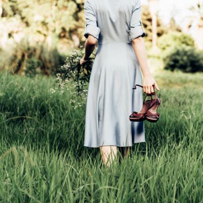 Frau schlendert über eine Wiese