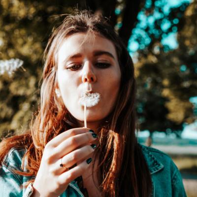 Junge Frau mit Pusteblume im Sommer