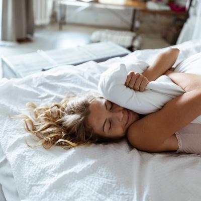 Frau im Bett mit Kissen im Arm