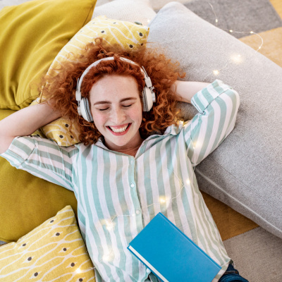 Frau liegt mit Kopfhörern auf dem Sofa