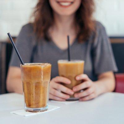 Frau sitzt am Tisch mit zwei Eiskaffee